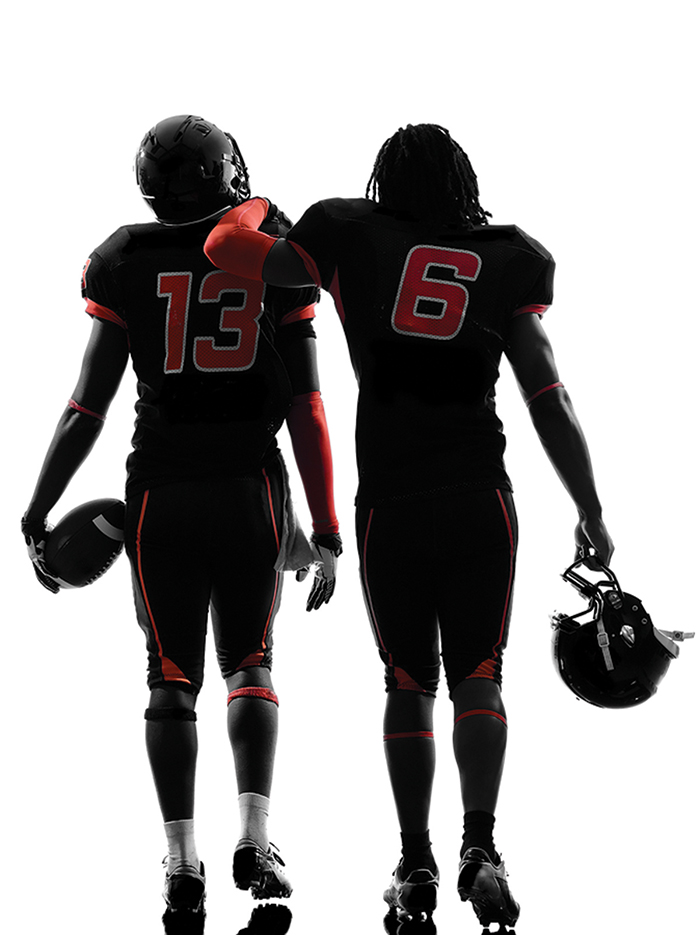two american football players walking rear view in silhouette sh