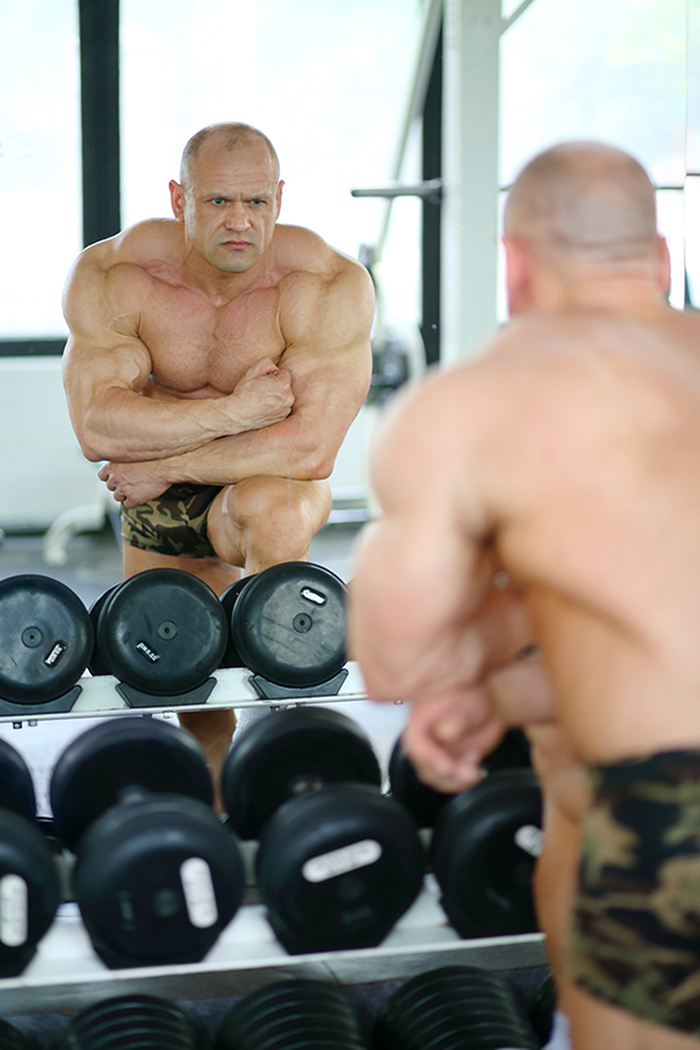 Middleaged bodybuilder in shorts looks into mirror at his muscle