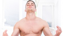 young handsome muscular half naked man doing yoga