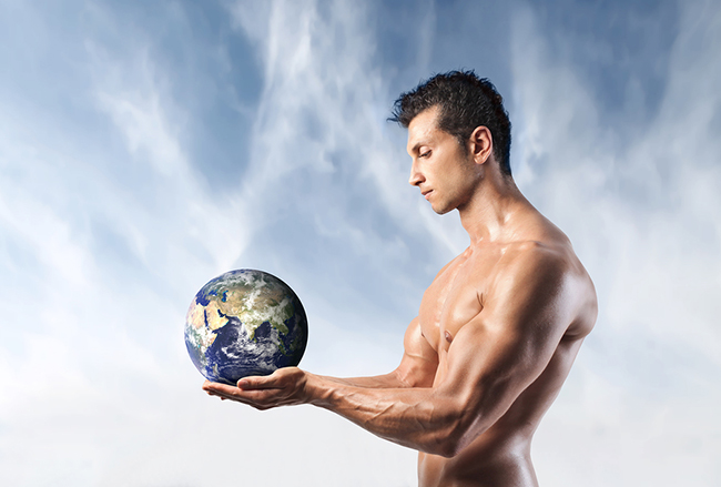 Handsome muscular man holding the Earth in his hands
